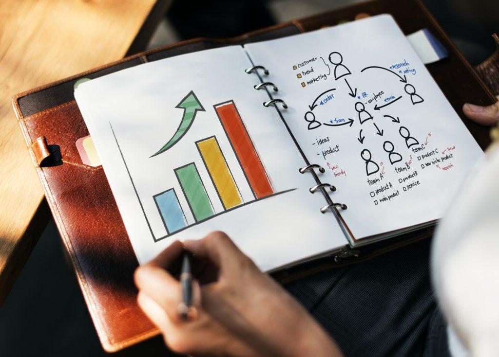 човек с тефтер прави бизнес план за бизнеса си